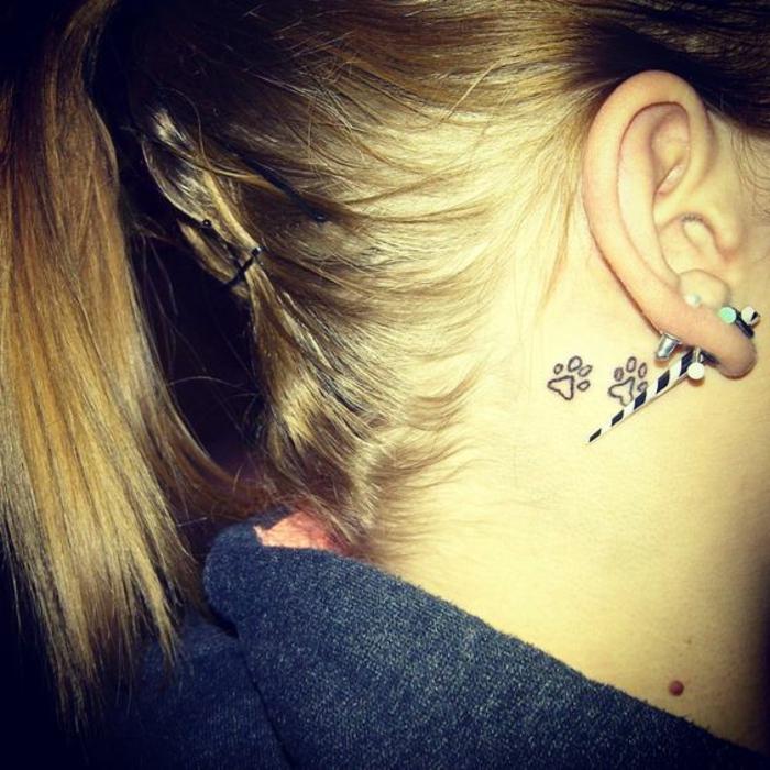 tatouage simple, deux pattes stylisées deriière l'oreille, piercing oreille original