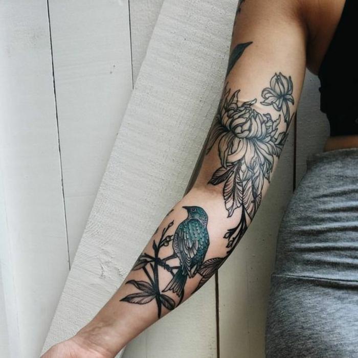 tattoo signification, jardin fleuri tatoué sur le bras, oiseau et pivoines