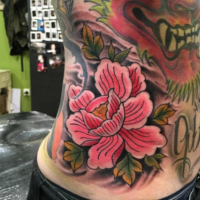 tattoo signification, tatouage fleurs sur la torse, pivoines roses fleuries et lion féroce
