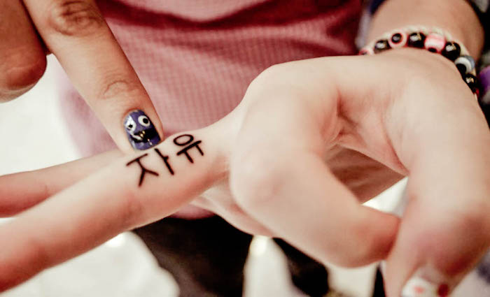 tatouage discret doigt symbole tattoo lettrage doigts
