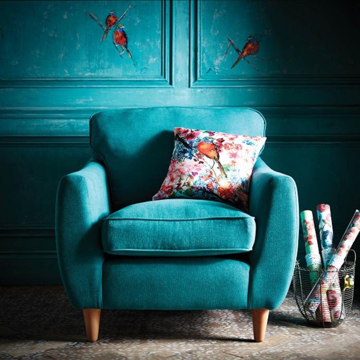 un fauteuil bleu sarcelle élégant associé à un coussin imprimé à motif floral
