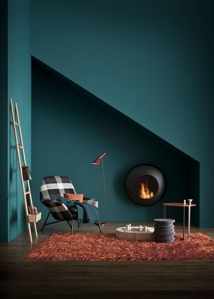 intérieur sombre et chic en bleu paon, gris et couleur terre de sienne, niche géométrique qui abrite une cheminée ronde