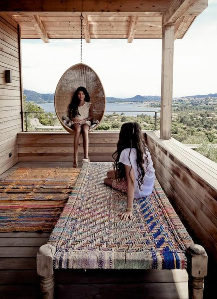 terrasse fermee avec chaise oeuf en canne d osier et lit en bois rude tressé