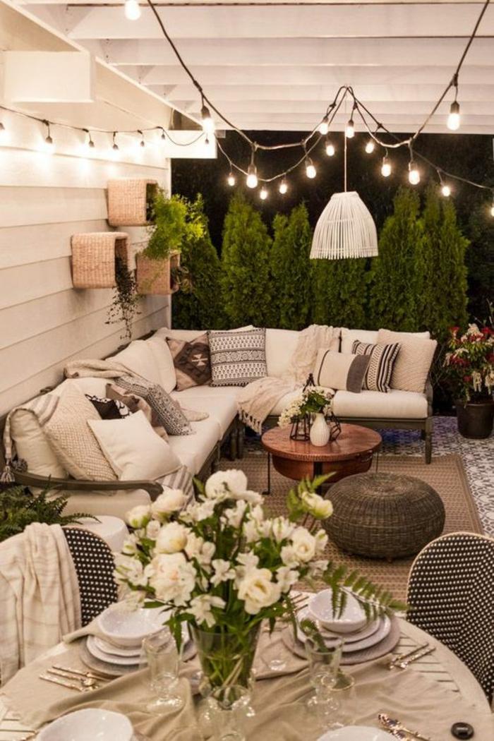 terrasse fermee avec meuble de jardin canapé angulaire et beaucoup de coussins
