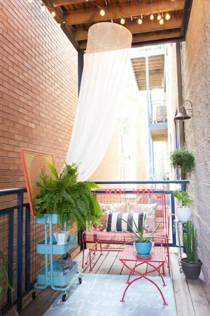 terasse couverte avec moustiquaire et porte plante bleu table et canapé rouges