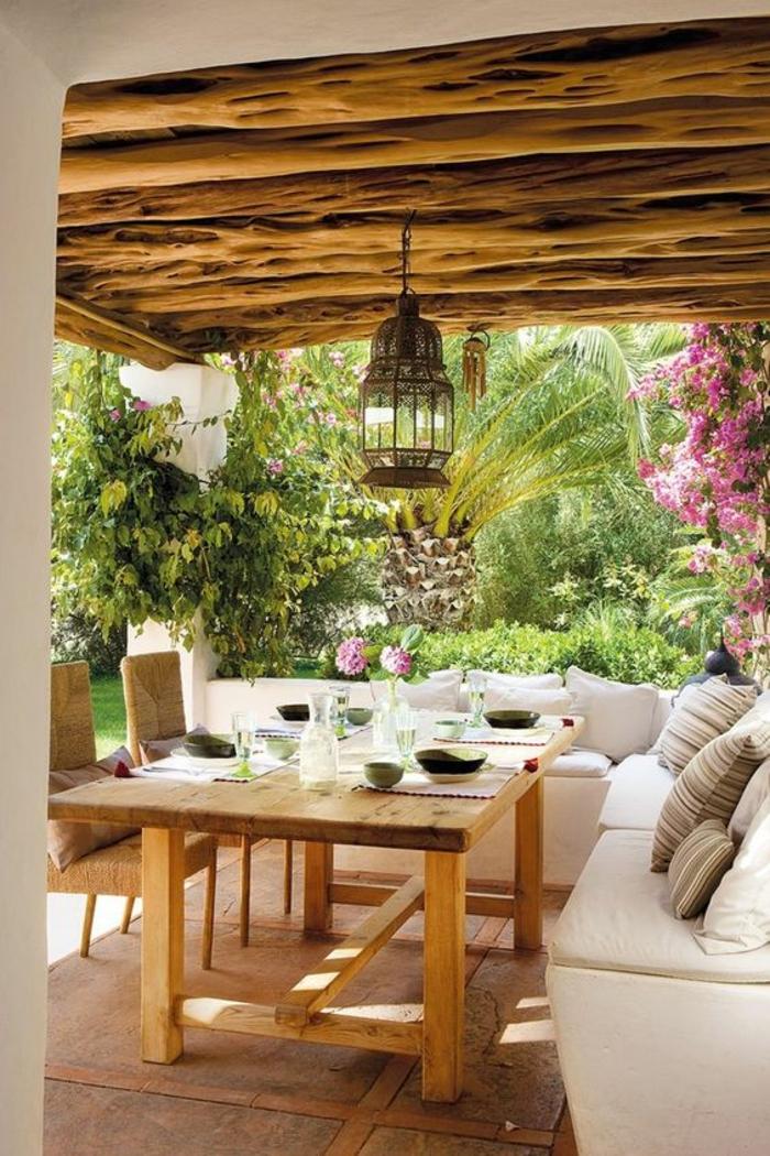 terrasse abritée avec des poutres au plafond et des meubles angulaires en blanc