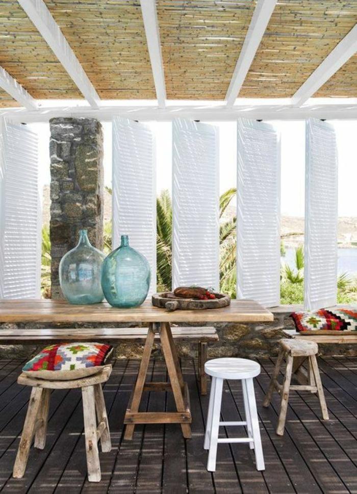 terrasse fermee avec le plafond tressé et des volets en tissu blanc