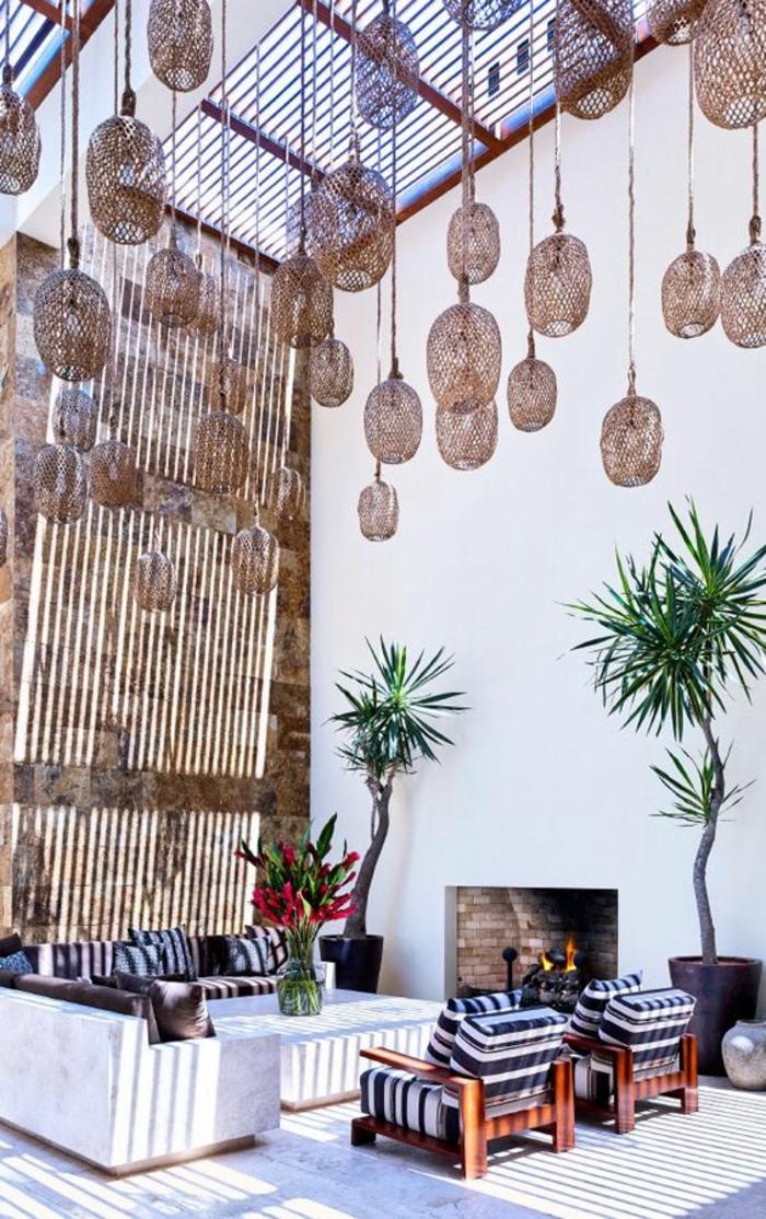 terasse couverte décorée avec des luminaires en rotin suspendus plafond très haut