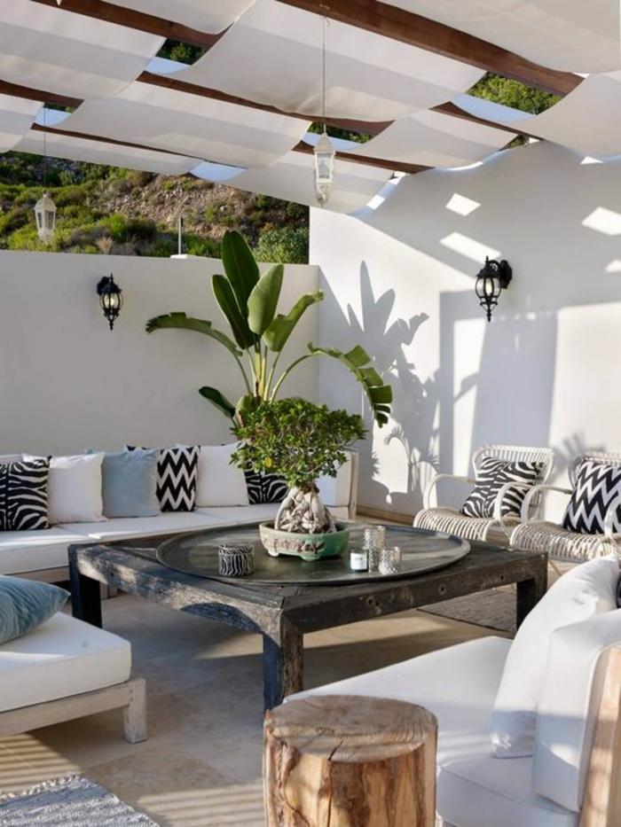 terasse couverte avec des tissus blancs comme des voiles de bateau et une grande table carrée au centre