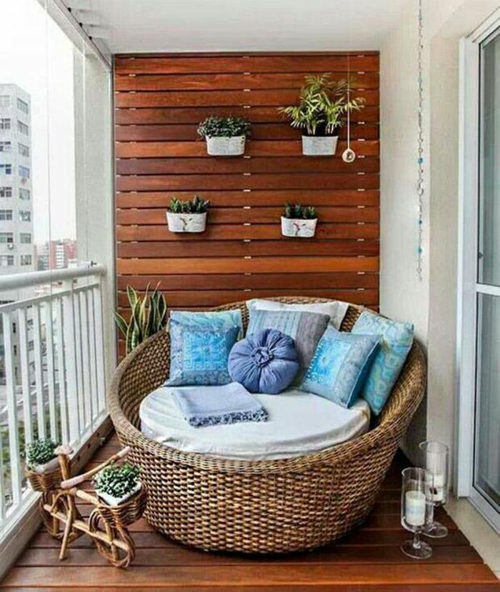 terasse couverte avec grand lit rond en rotin plein de coussins ronds et carrés