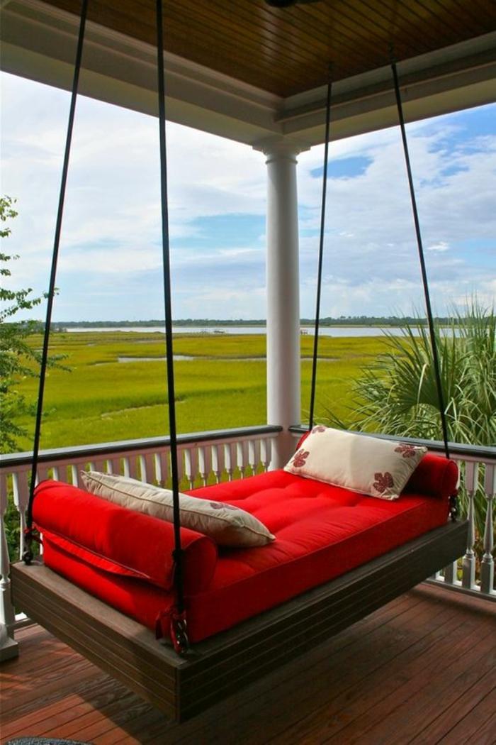 terrasse fermee avec lit en bois suspendu avec des cordes avec une vue magnifique sur un lac