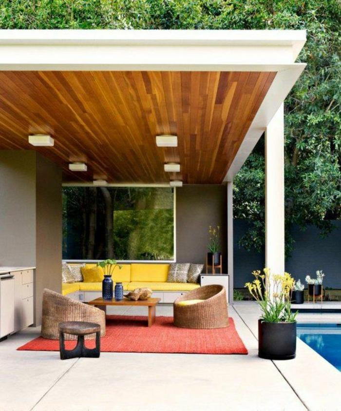 terasse couverte abritée avec toit revetu de bois PVC et des fauteuils ronds en rotin