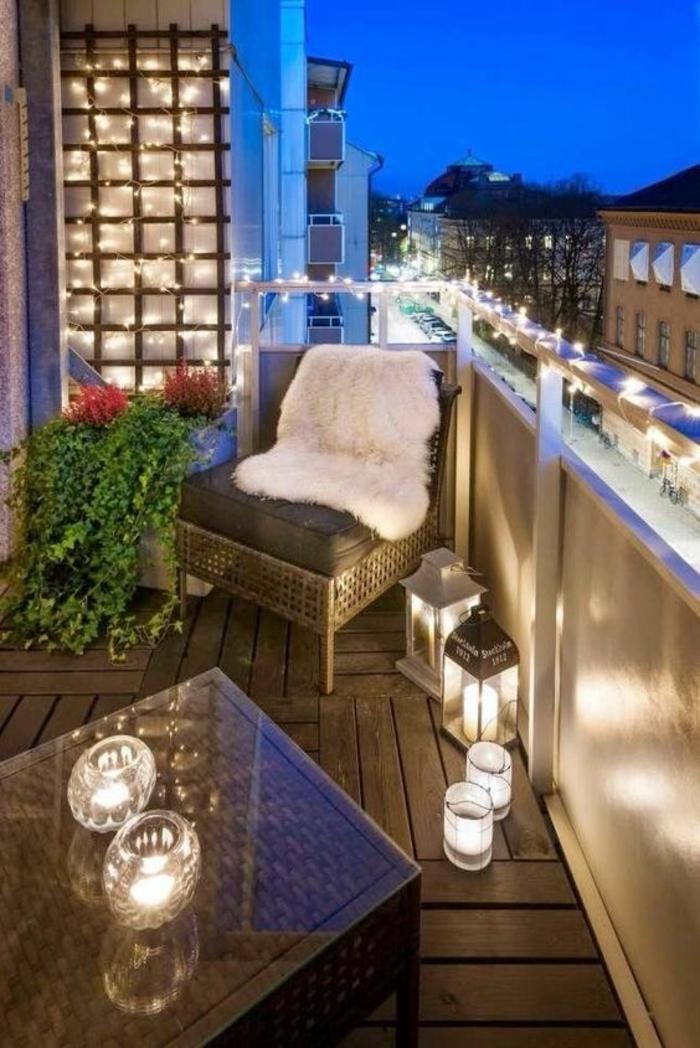 terrasse abritée balcon illuminé avec des ampoules blanches et un revetement du sol en bois synthétique
