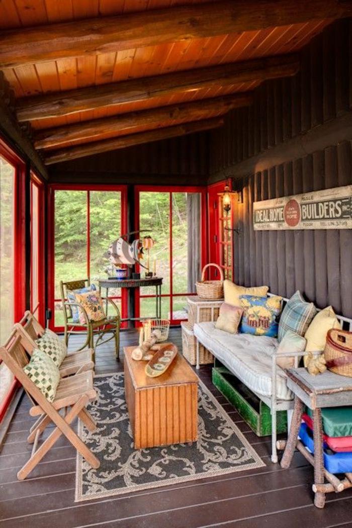 terasse fermee couverte avec toit en pente et des meubles de jardin en bois