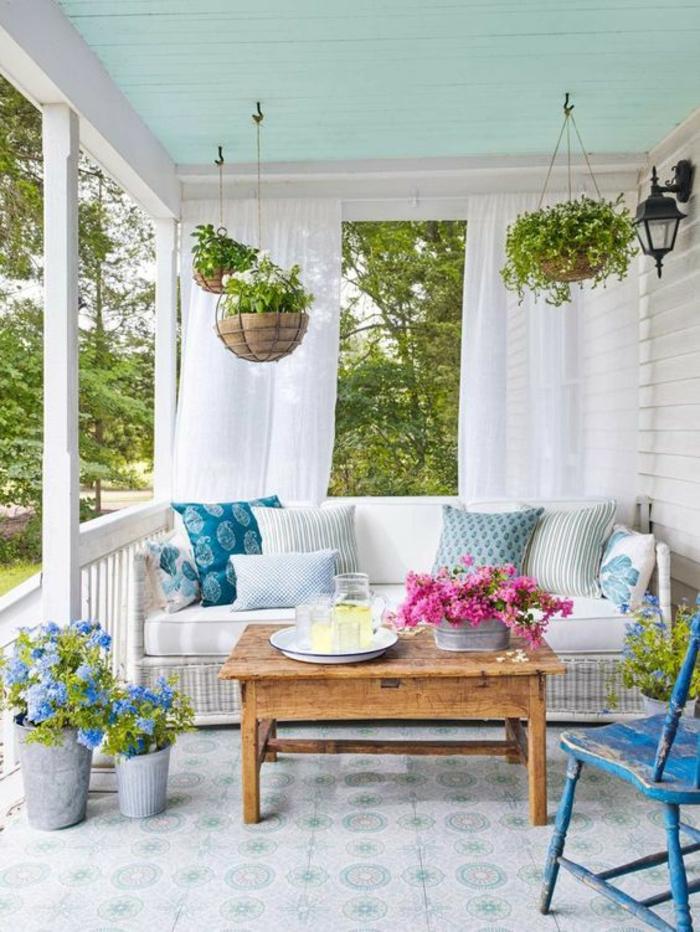 terrasse pergola veranda avec canapé en rotin blanc et des pots de plantes suspendus tressés