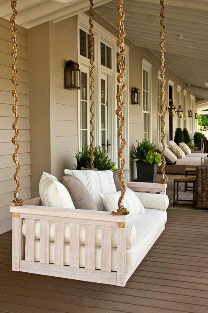 terrasse fermee couverte avec canapé suspendu avec beaucoup de coussins