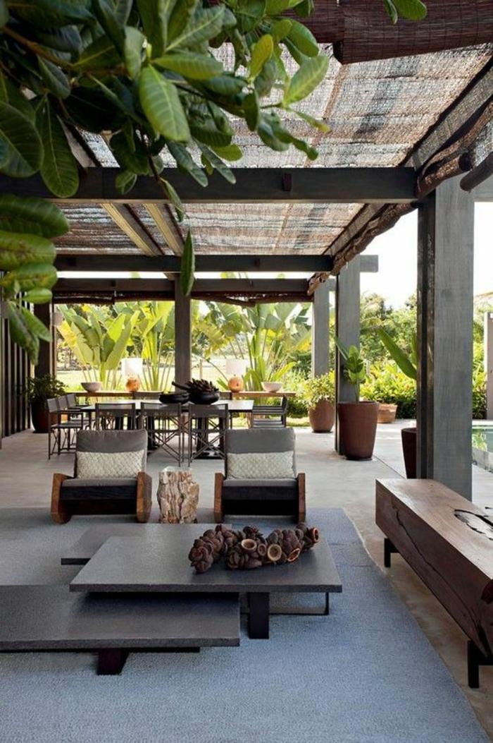 terrasse fermee avec des meubles massifs et des tables formées de trois panneaux gris