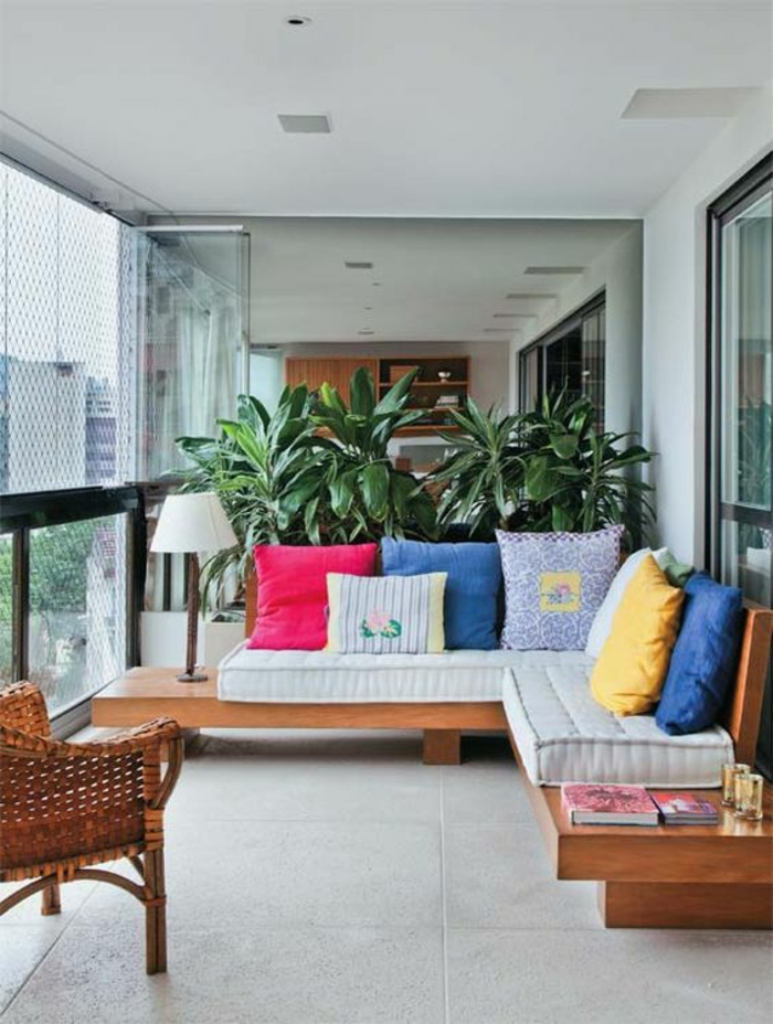 terrasse couverte avec des meubles en bois marron clair avec beaucoup de coussins multicolores