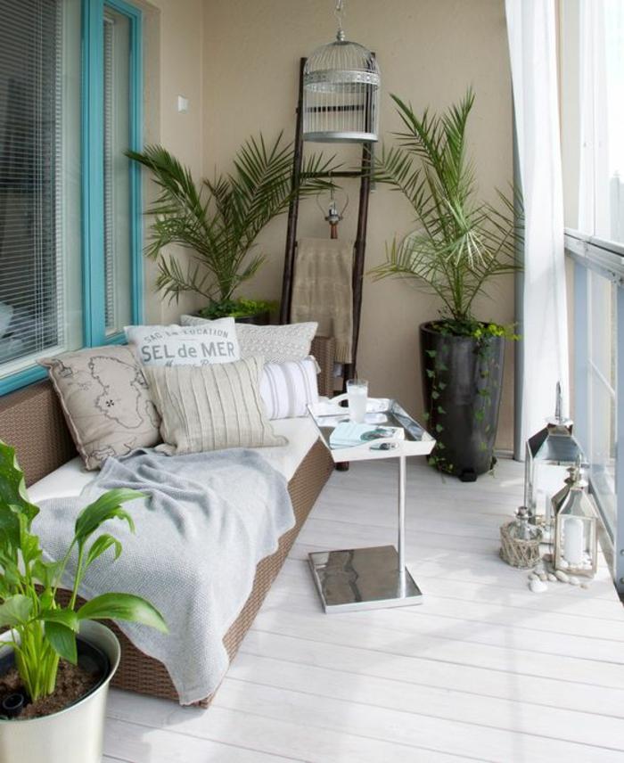 terrasse couverte avec canapé et coussins en couleur blanc crème et beige