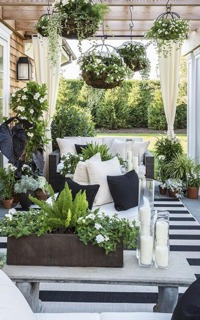terrasse couverte avec des pots suspendus et des meubles douillets
