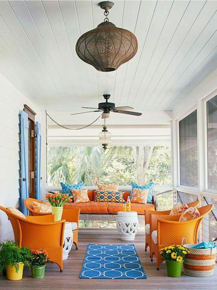 terrasse couverte avec des meubles en couleurs fruitées et un petit tapis bleu au centre