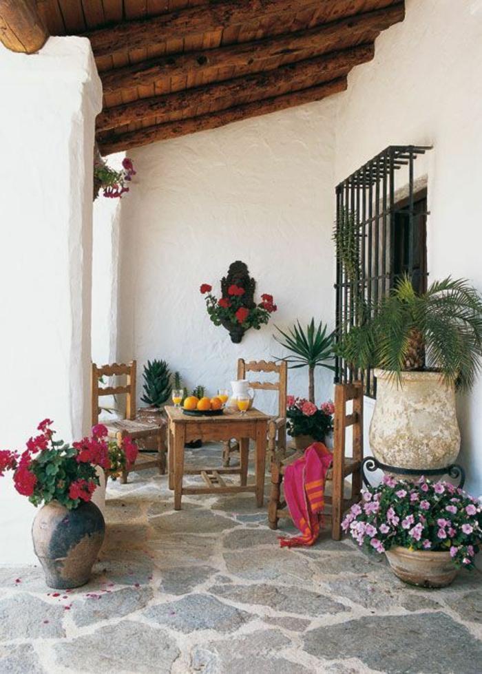terasse couverte avec des pots de fleurs et des colonnes blanches