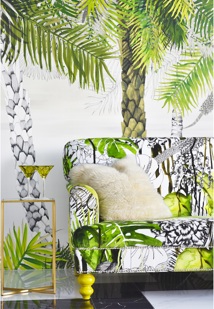 papier peint tropical, table en verre et laiton, coussin en fausse fourrure blanche, canapé à motifs tropicales en blanc et vert