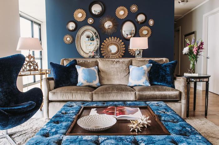 fauteuil velours, murs blancs avec une partie peint en bleu, mur de miroirs soleil, table noire en verre, bouquet de fleur, vase en verre