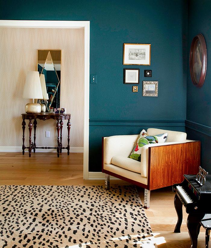 deco moderne, mur peint en bleu foncé, lampe de chevet en beige et cuivre, miroir rectangulaire à motifs géometriques