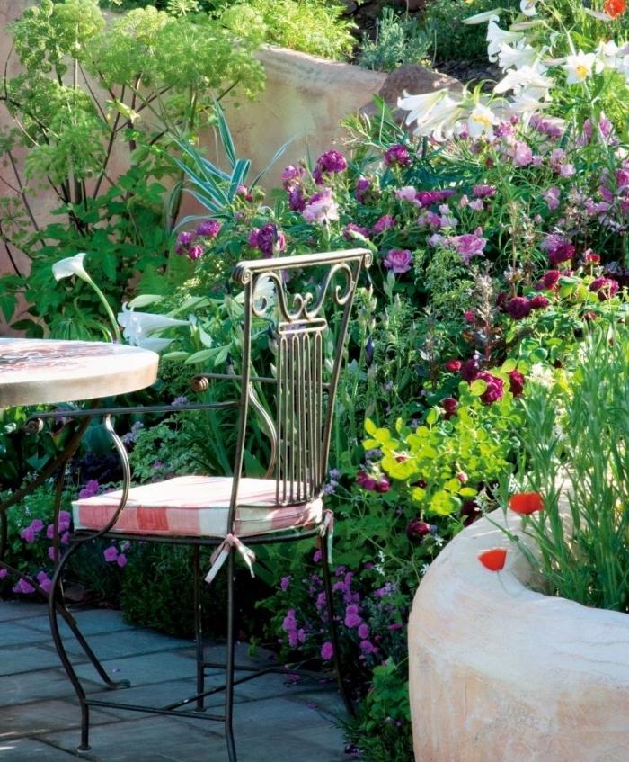 une végétation florissante, disposée à l anglaise, plusieurs arbustes fleuris, fleurs, salon de jardin, constitué de table et chaise en metal
