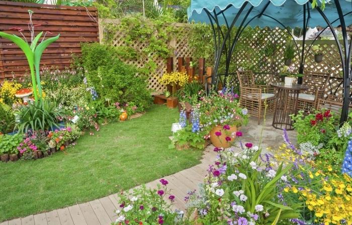 aménager son jardin, chemin de planches de bois, gazon et parterre de fleurs, sculptures jardin, gazebo, chaises et table en bois, brise-vue fleurie