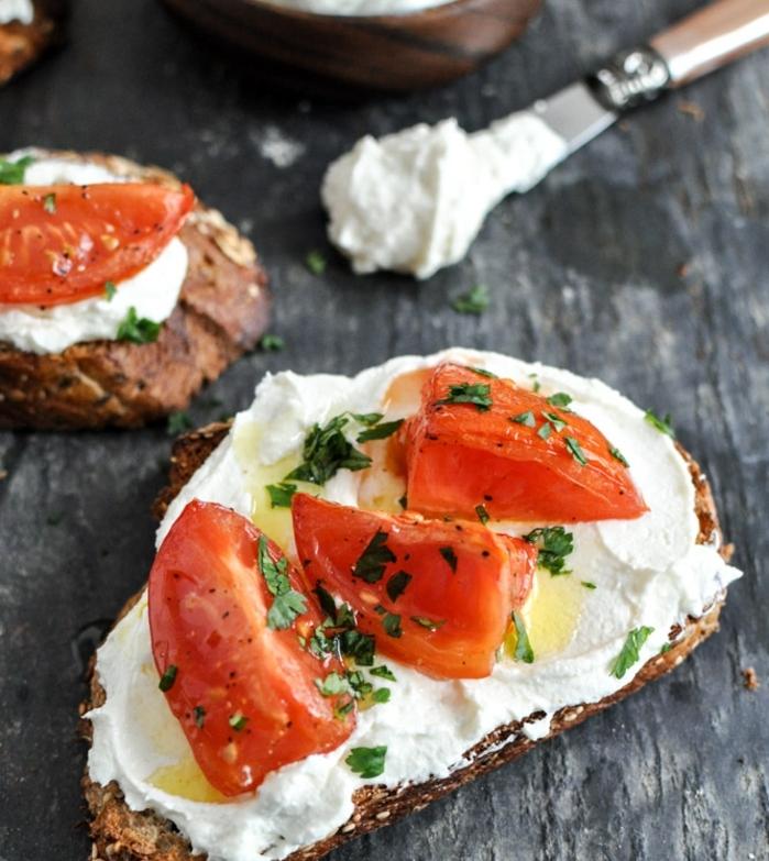 un toast, pain, tartiné de mélange de fromage feta émietté et fromage à la crème avec des tomates et persil, recette tapas faicle