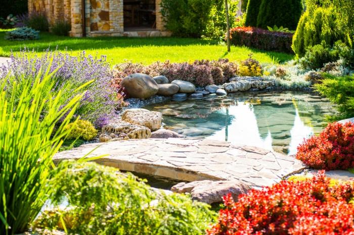amenagement jardin exterieur avec un étang et un pont en pierre, plusieurs pierres, arbustes et arbres