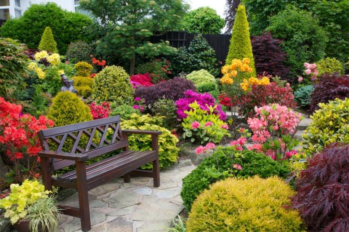 aménager son jardin, un paysage rustique banc en bois entouré de toute sorte de fleur set d arbustes fleuris, chemin de pierres