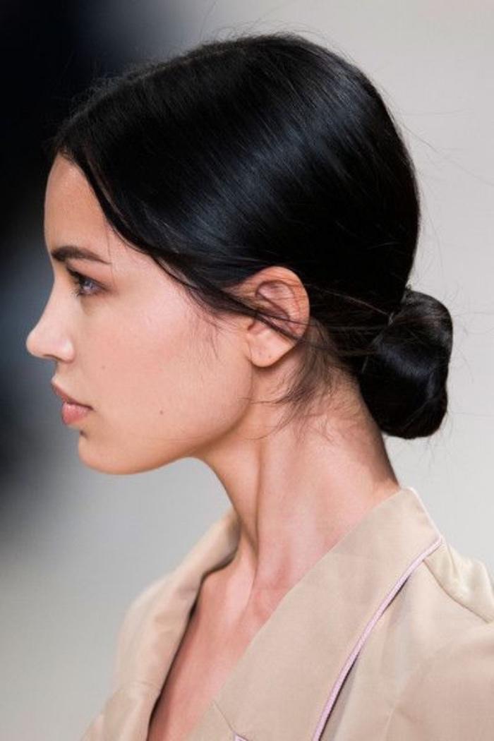 coiffure facile et rigide, chignon bas sur des cheveux noirs lisses, mèches de cheveux des deux cotés