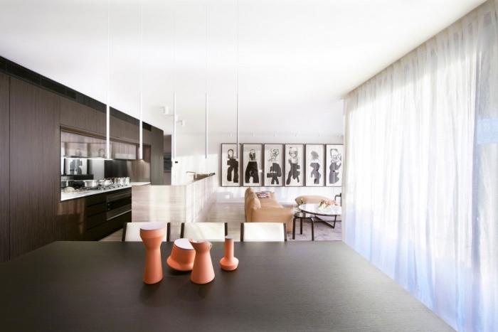 petite cuisine équipée en bois marron foncé avec ilot de cuisine gris clairm coin salon avec canapé et tabouret en cuir, table basse, coin salle à manger avec table en bois massive et chaises blanches