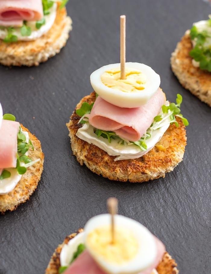 idée comment faire des tapas, sandwiches, pain grillée, toast rond, avec du fromage de chèvre, jambon, oeuf dur, cresson et moutarde