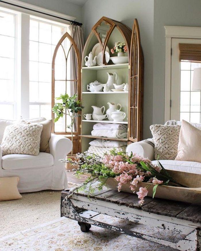 salon shabby chic, vaisselier en bois avec vaisselle blanche, canapés shabby chic blancs, table patinée, bouquet de fleurs rose