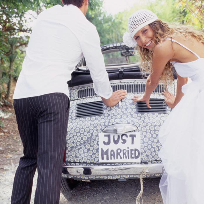 photo originale du jeune couple de mariés qui poussent une voiture de noce rétro