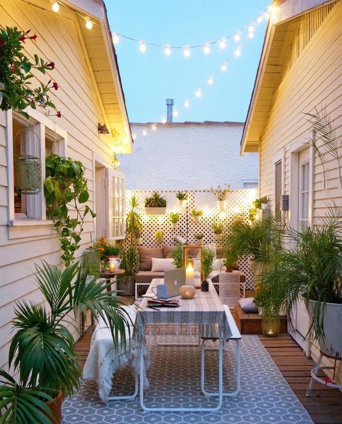 aménager un petit jardin avec des guirlandes aux ampoules avec des pots aux plantes vertes