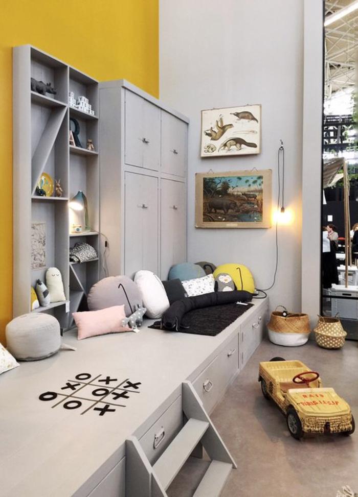 décoration chambre garçon en jaune et taupe grand espace avec des jouets et des tableaux theme sciences aux murs