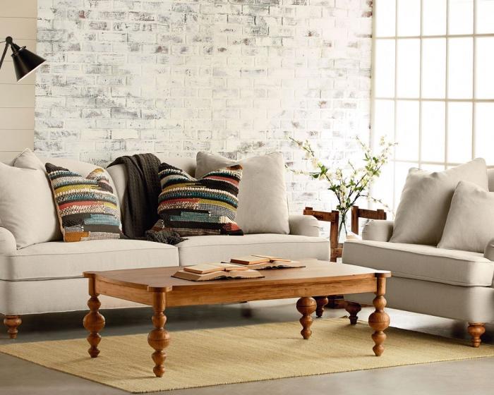 tapis couleur ecru, revêtement sol, canapé et fauteuil gris, table basse bois vintage, mur de briques blanchis, coussins bohème