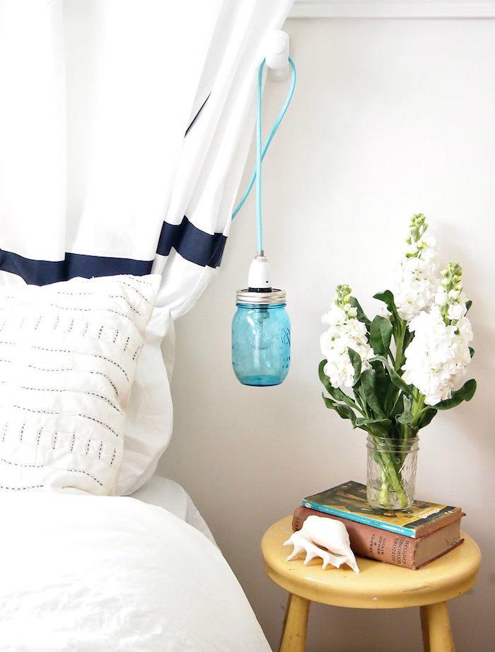 déco chambre à coucher, couverture et linge de lit en blanc, bouquet de fleurs blancs, livres et coquillage