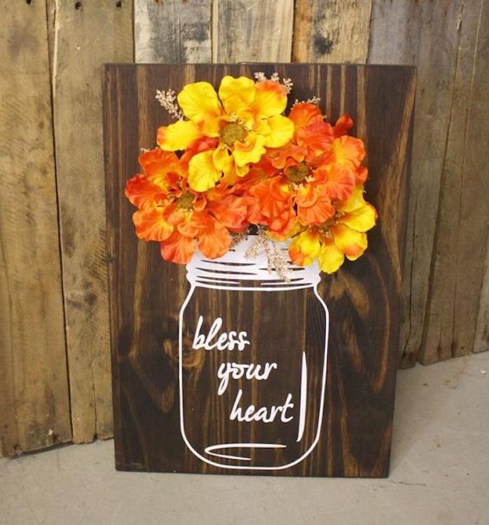 une planche en bois marron avec dessin pot, vase au feutre blanc et bouquet de fleurs jaune et orange, deco automne a faire soi meme