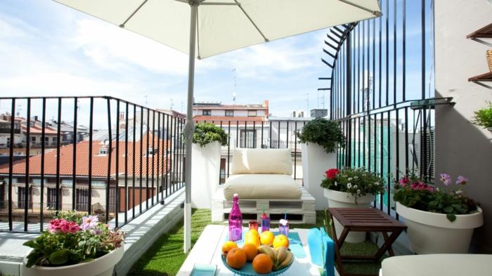 balcon, amenagement terrasse, revêtement gazon artificiel, fauteuil en palette avec assise blanc cassé, table basse en palette, plusieurs pots de fleurs, parasol blanc
