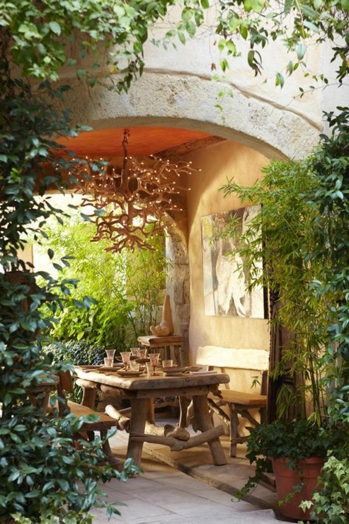 idee de parterre de fleur avec meubles de jardin sous une grande arche