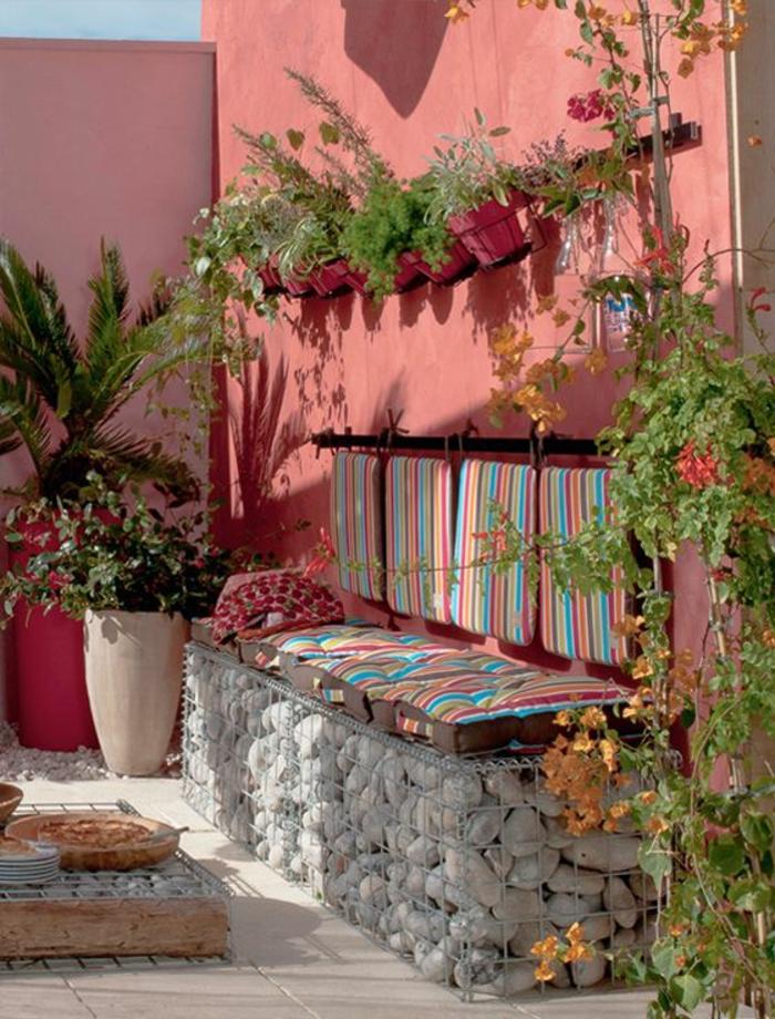 exemple d aménagement de jardin avec des murs en couleur rose et des coussins pour le banc en pierre aux rayures pastels