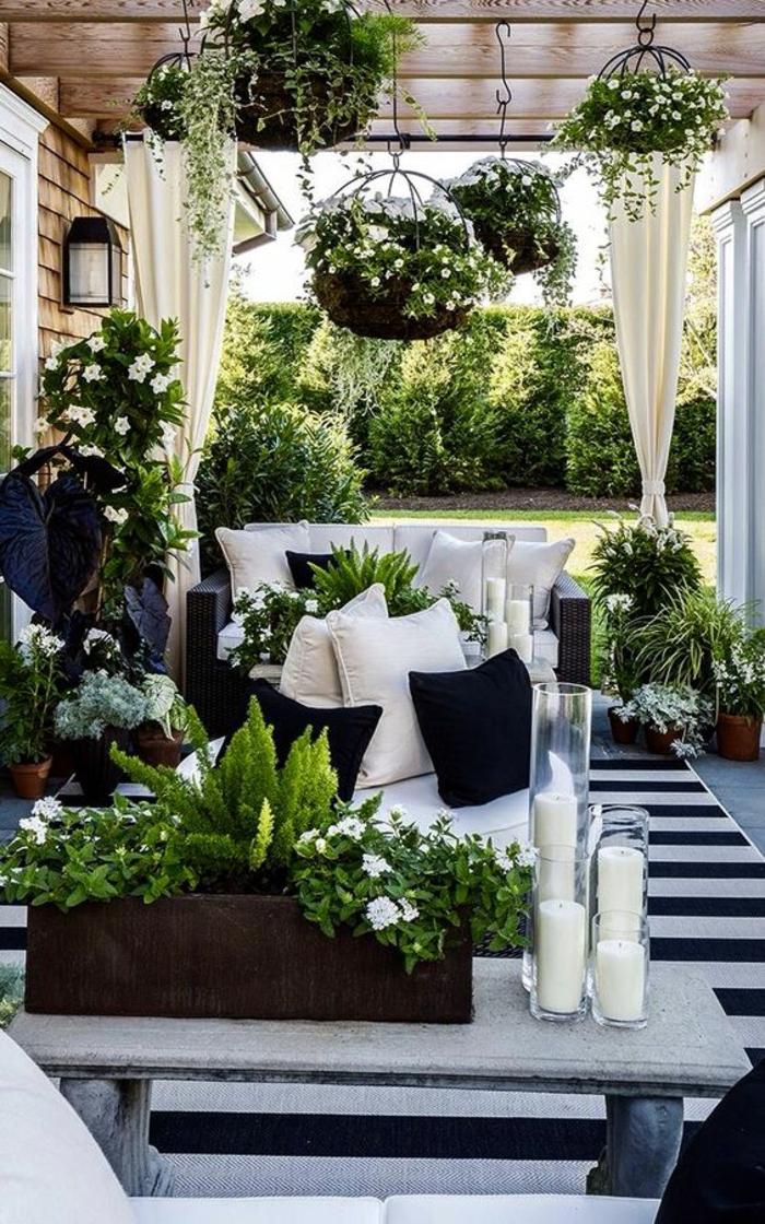 amenagement jardin avec des grands poufs et des coussins en bleu et blanc