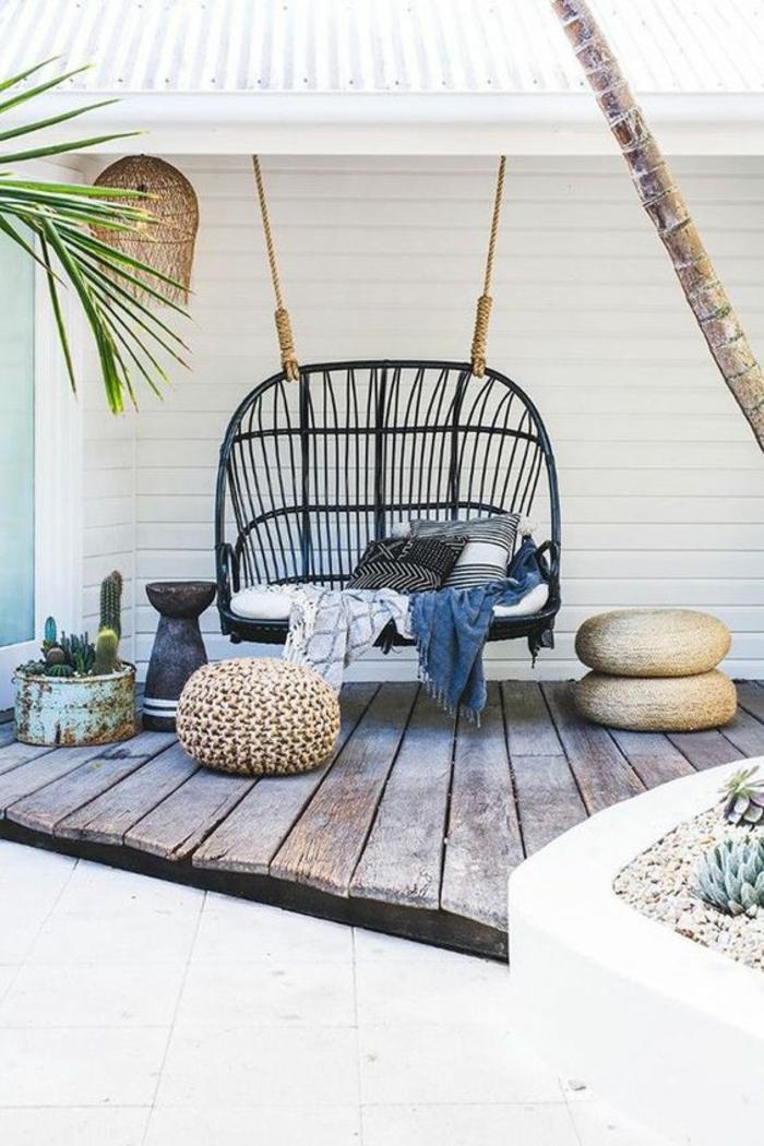 aménager son jardin avec un canapé suspendu en bleu avec un grand matelas blanc