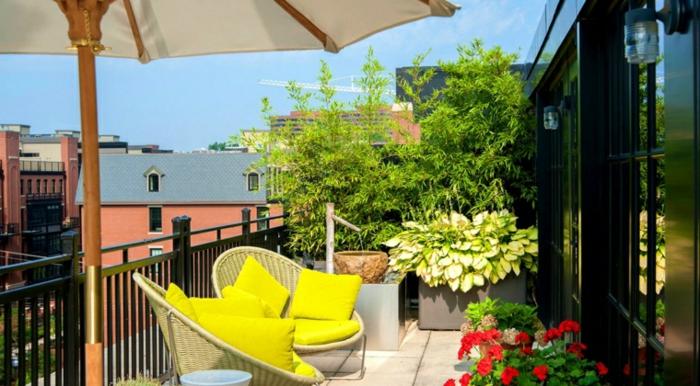 deco terrasse sur un petit balcon avec revêtement en béton, chaises en rotin avec coussins jaunes, parasol, bambou, plantes et fleurs, petite fontaine